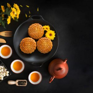 Overhead view mid autumn mooncake and tea set on black texture table top background. Text space image.